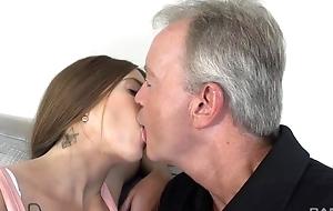 Sex-starved brunette pleasuring elderly man on the sofa