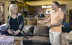 Blonde-haired grown up pleases tattooed dude on leather couch